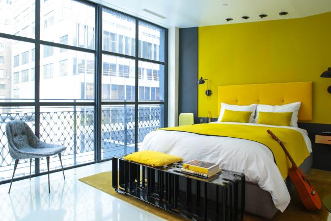 Прекрасное сочетание желтого с серым в интерьере спальни