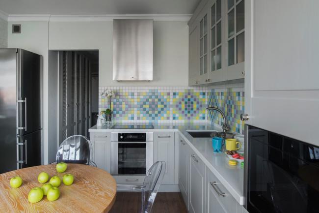 Традиционную кухню освежает яркий узор из плитки на стене