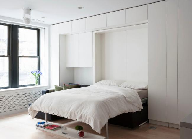 Минималистичный интерьер с кроватью, вмонтированной в шкаф
