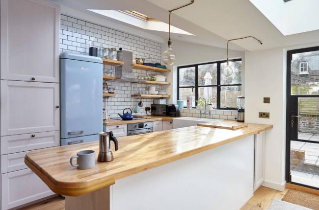 Позитивное настроение просматривается в оформлении кухонного пространства, разбавленного дерево ми цветным холодильником