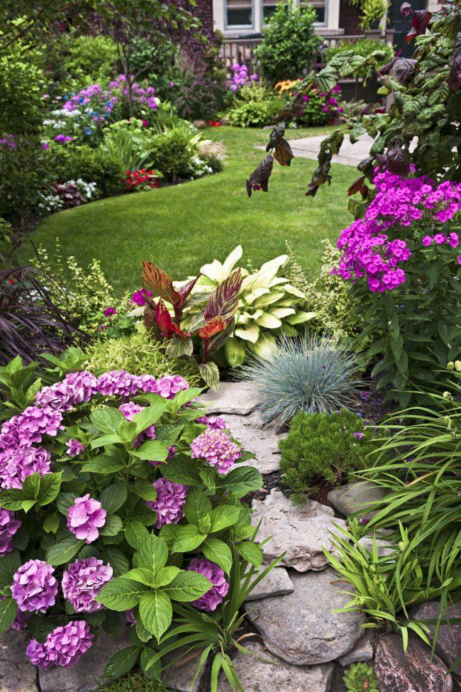 Аккуратно сложенные камни в форме полукруга в композиции с цветущими растениями - эффектна клубма у вас во дворе
