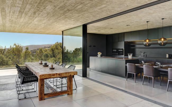 Кухня с панорамным остеклением и темной мебелью смотрится очень стильно
