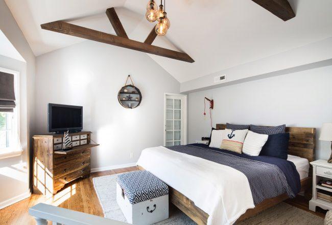 Мебель из грубого дерева и балки отлично впишутся в интерьер небольшой спальни в морском стиле или любом рустикальном интерьере