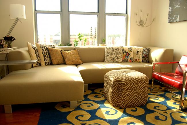 Мягкая мебель светло-бежевого цвета с большим количеством подушек