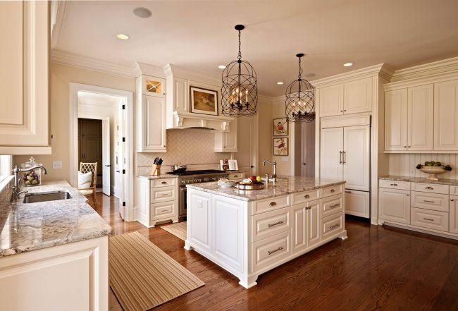 Лаконичный и элегантный кухонный интерьер цвета слоновой кости. Светлые мраморные столешницы и кованые винтажные светильники - характерные акценты для подобного решения