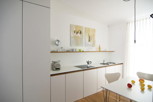 Белый минималистичный интерьер с квадратным обеденным столом