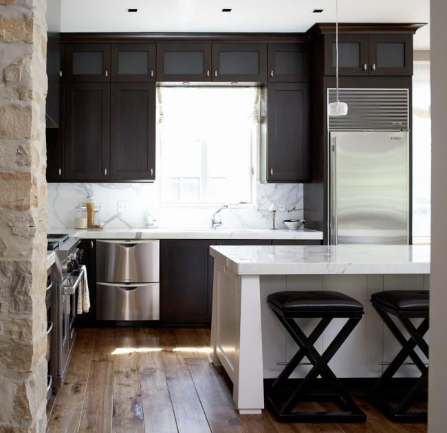 Стильное решение - массивный стол, играющий роль разделителя пространства между кухней и гостиной