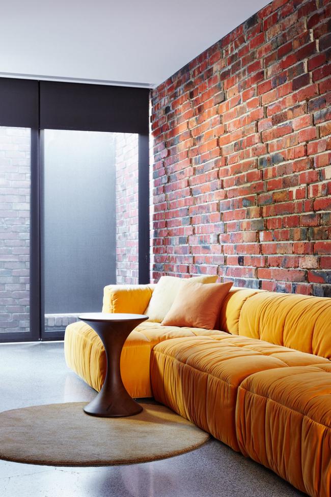 Яркий диван на фоне кирпичной стены