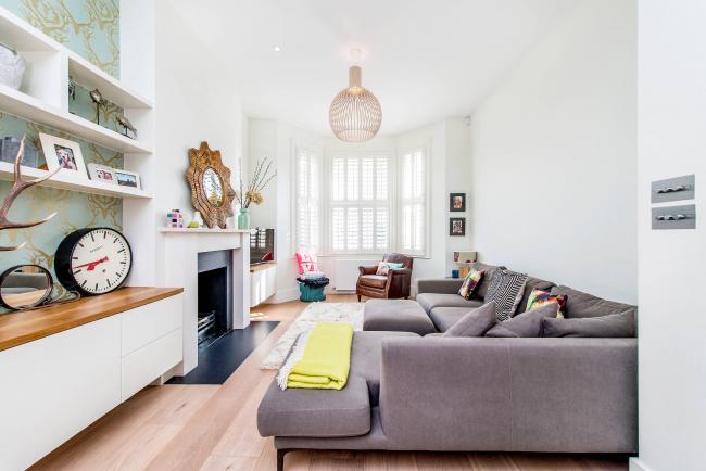 Угловой диван в интерьере зала прямоугольной формы