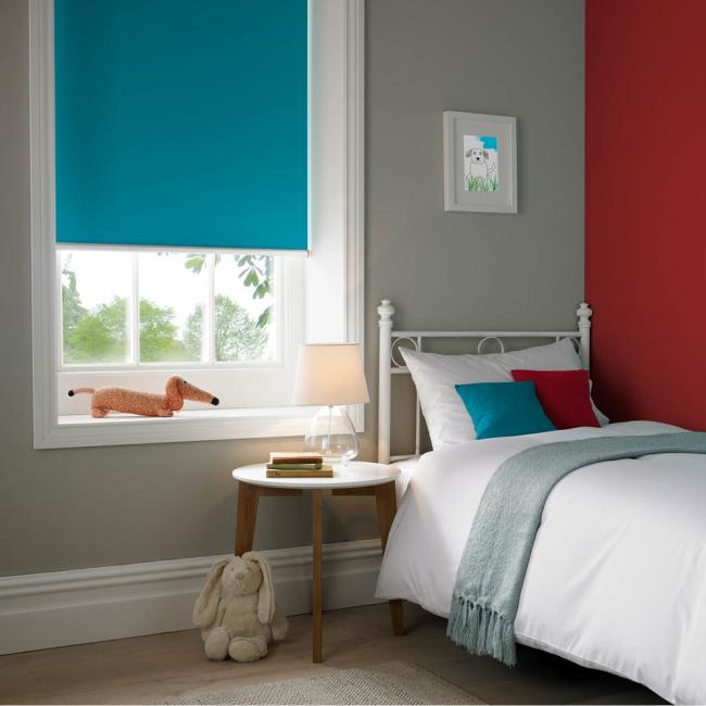 Красный цвет акцентной стены в детской комнате дополняет голубая роллета и декоративные подушки