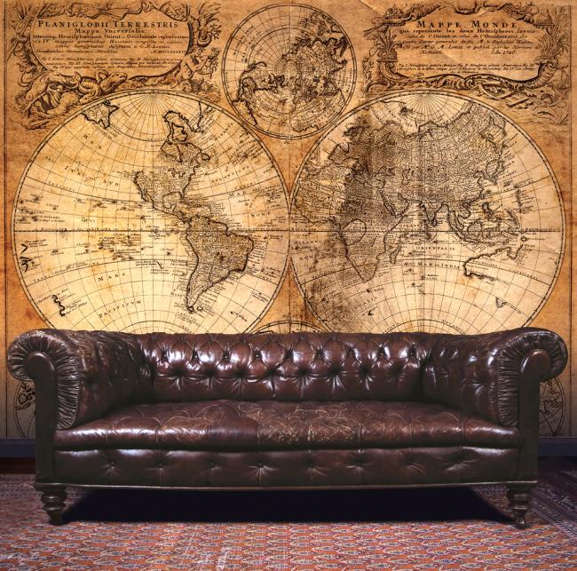 Роскошный диван Честерфилд на фоне старинной карты мира