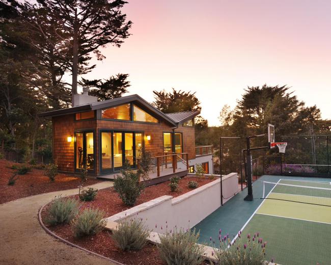 Загородный дом с баскетбольной площадкой, расположенный на склоне