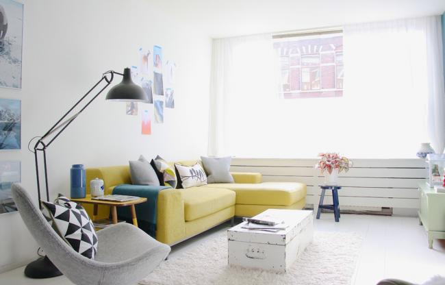 Желтый угловой диван в интерьере зала, оформленном в скандинавском стиле