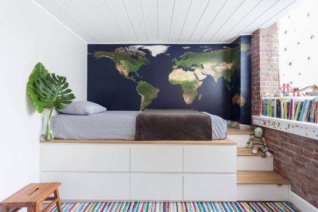 Стильная комната для мальчика с картой мира на одной из стен вместо обоев и кроватью на подиуме