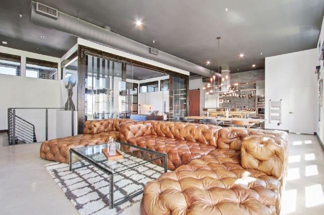 Угловой роскошный диван из кожи в дизайне квартиры-студии