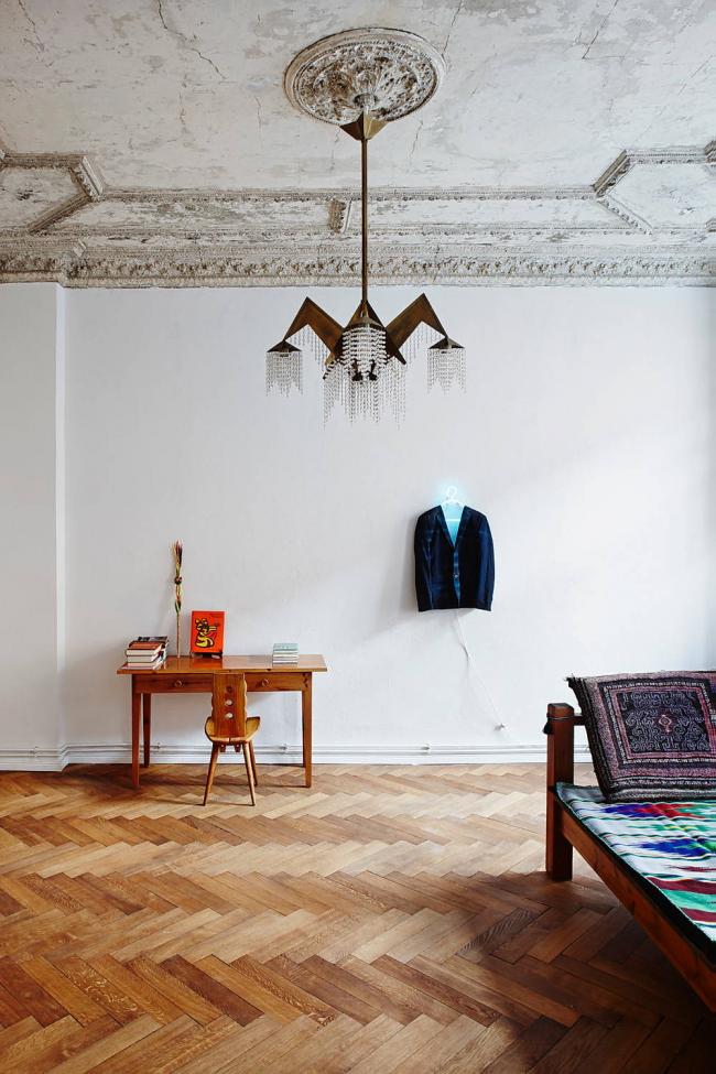 Авангардная форма люстры в классической обстановке: состаренный потолок с лепниной, нейтральные белые стены, наборной паркет на полу