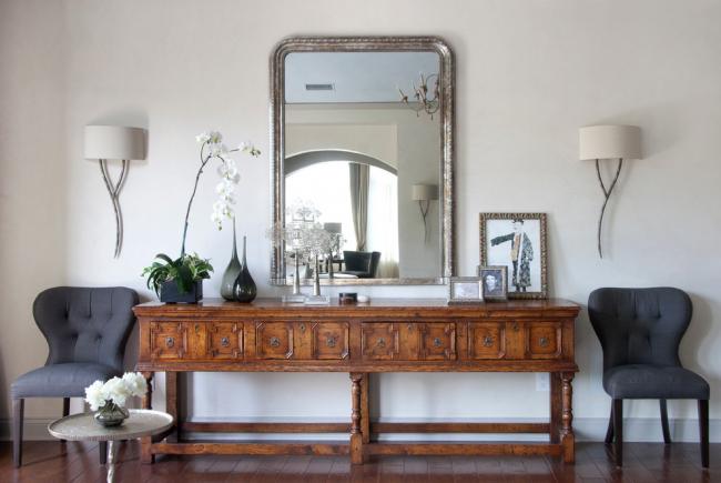 Состаренное зеркало и роскошный деревянный комод ручной работы смотрятся очень гармонично