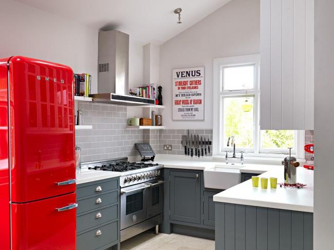 Серый кухонный фартук с имитацией кирпичной кладки, серый гарнитур с белой столешницей, металлический блеск бытовой техники – простой и функциональный дизайн, подчеркивающий яркие всплески. Красный ретрохолодильник – уникальный предмет в кухонном интерьере