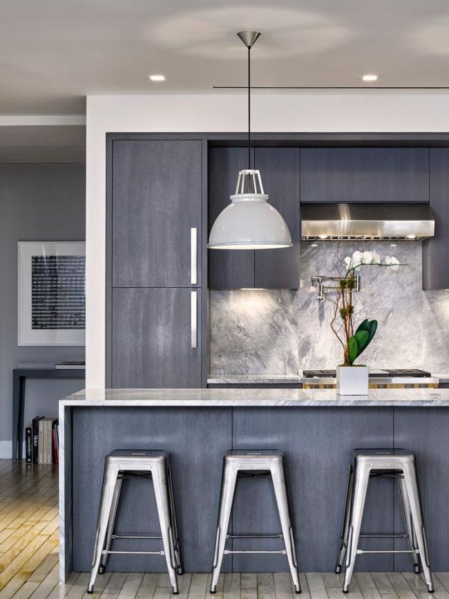 Серый матовый кухонный гарнитур и каменный «живописный» фартук скрывают отпечатки пальцев и брызги воды