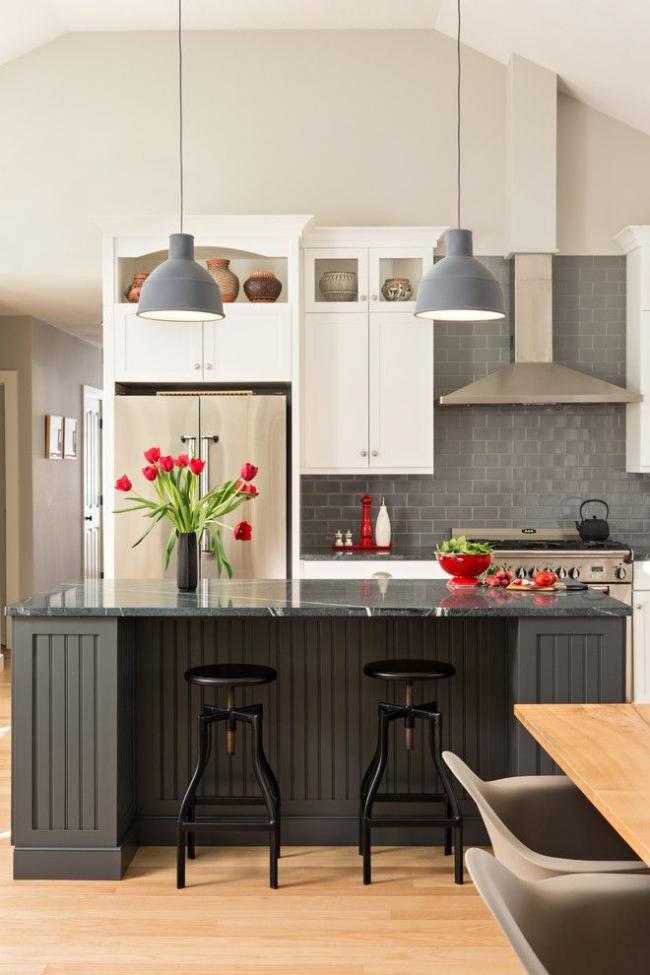 Серый кухонный гарнитур, серые лампы, металлическая бытовая техника скомпонованные с ярко-красными кухонными аксессуарами