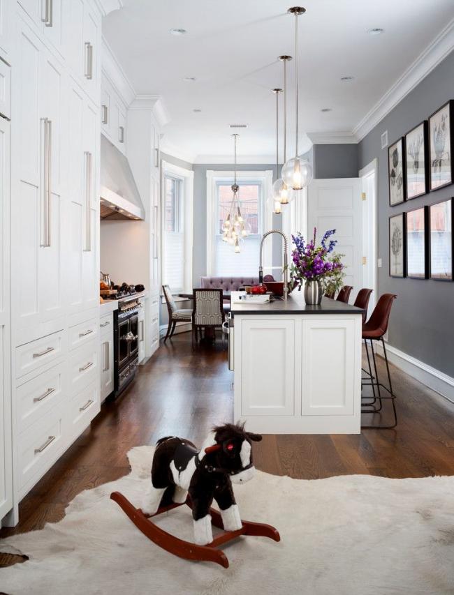 Однотонные серые стены, деревянный пол, белый кухонный гарнитур, подвесные лампы со стеклянным абажуром – общее нейтральное оформление современной кухни. Акценты: сиреневый диван, геометрическая обивка обеденных стульев, высокие коричневые анатомические стулья, иллюстрации на стенах и букет живых цветов