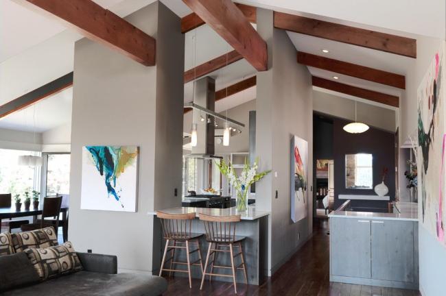 Лаконичная современная кухня: два оттенка серого цвета в оформлении стен, холсты без рам с абстрактной живописью, шинная подвесная конструкция освещения и встроенные светильники, глянцевые столешницы и другие детали