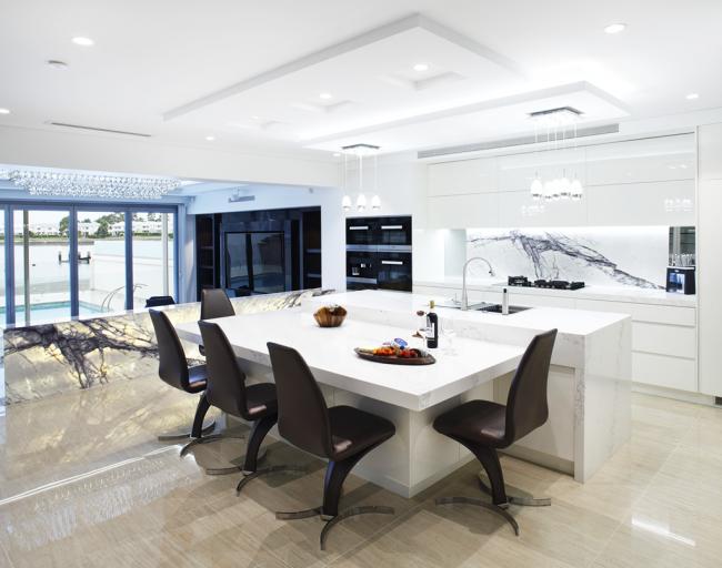 Интересное сочетание белого глянца и мрамора с подсветкой в современной кухне