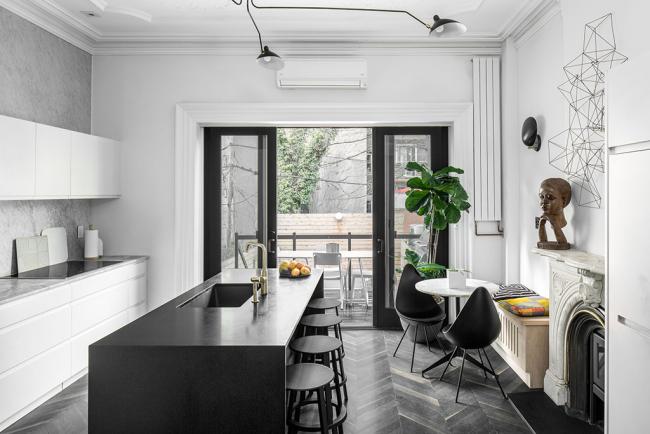 Классическое черно-белое оформление искусственно зонирует малогабаритную кухню