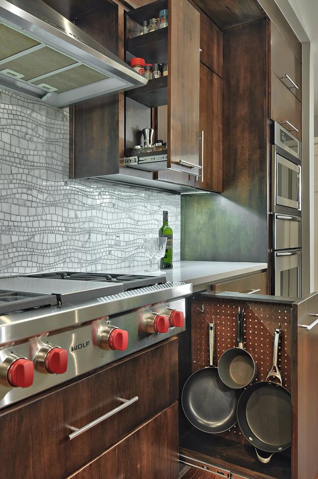 Хранить кухонные принадлежности удобно в подвешенному виде в узкой выдвижной ячейке возле плиты