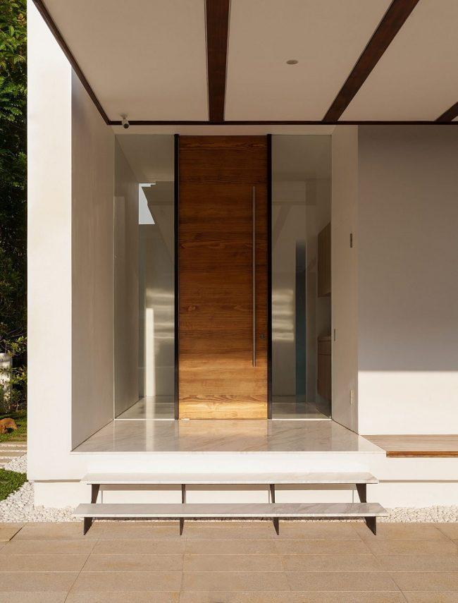 Узкая одинарная входная дверь с длинной металлической ручкой