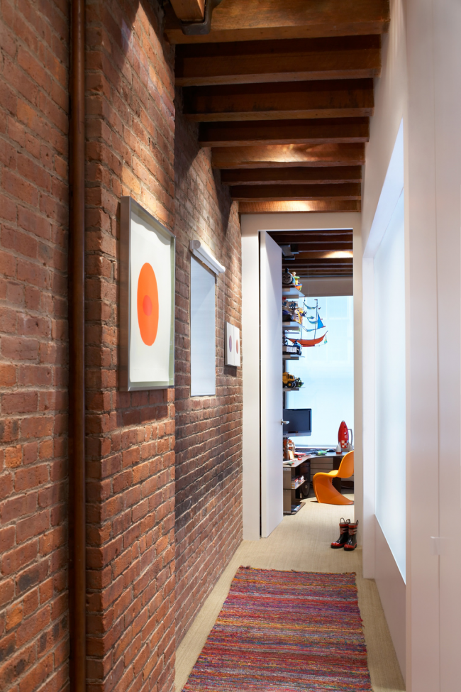 Равномерное точечное освещение в длинном коридоре с кирпичной кладкой на стенах и очень атмосферными деревянными балками под потолком