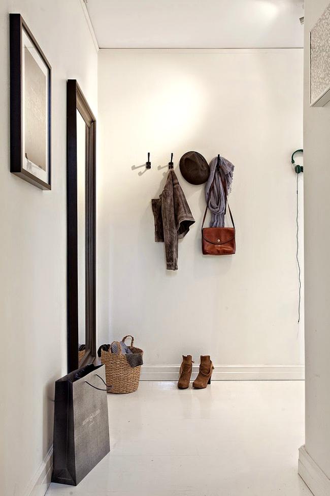 Небольшой коридор в светлых тонах с ярким освещением, размещенным на стыке с потолком одной из стен
