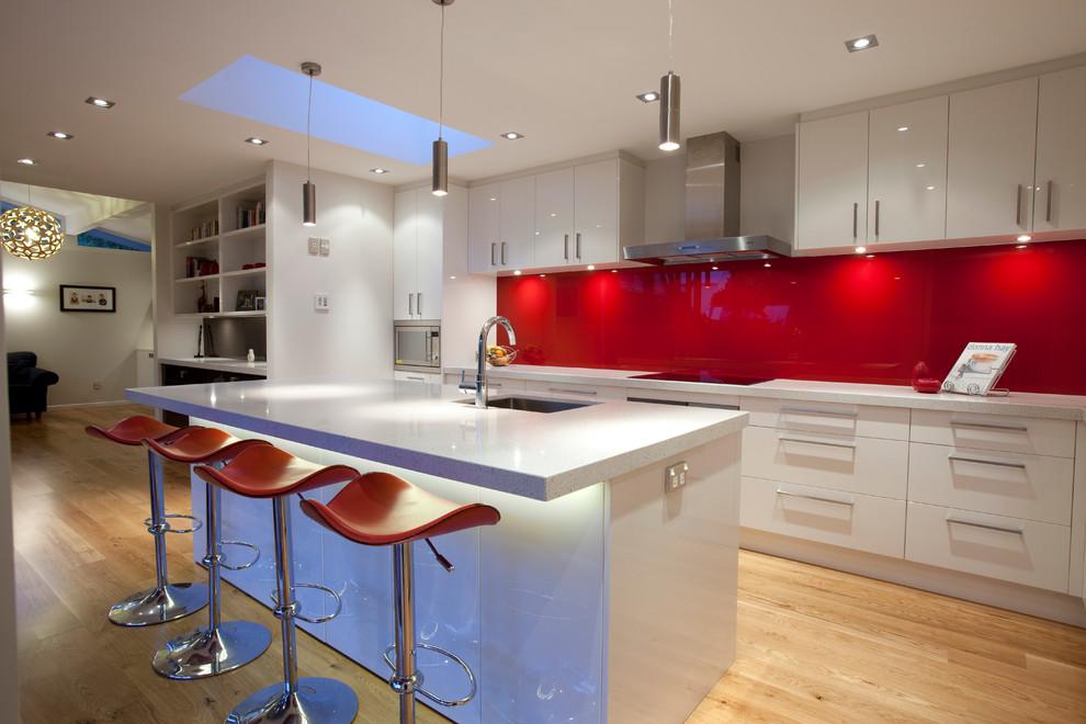 Красный кухонный фартук на фоне белой мебели смотрится очень эффектно