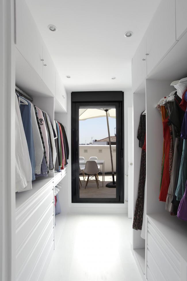 Небольшая гардеробная с вместительными шкафами и большим зеркалом