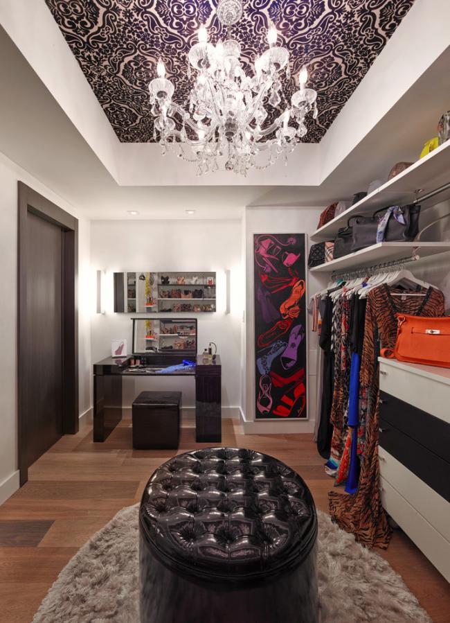 Уютная современная гардеробная комната с большим кожаным пуфом в центре комнаты