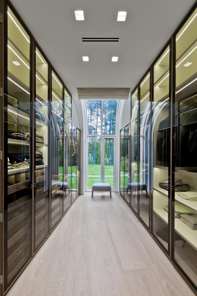 Вытянутая гардеробная с прозрачными шкафами по обе стороны комнаты
