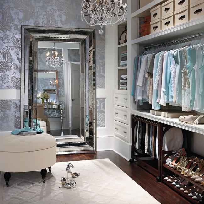 Классическая гардеробная с местами для хранения различных вещей большим зеркалом и мягким пуфом