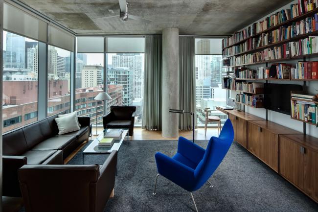 Контрастное синее кресло в сером оформлении гостиной стиля лофт