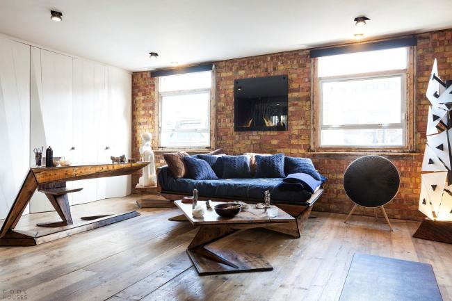 Деревянная мебель и кирпичная стена в оформлении гостиной стиля лофт
