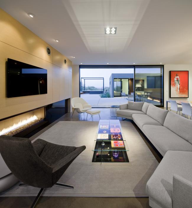 Еще один вариант стеклянного журнального столика с полочками позволяет видеть, что находится под столешницей. Это помогает поддерживать идеальный порядок в гостиной