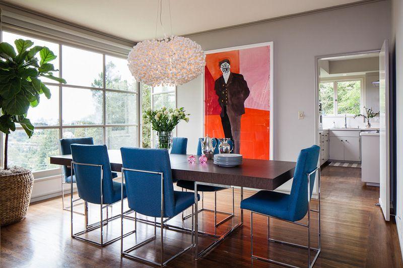 Модная столовая с дизайнерской люстрой и яркой картиной