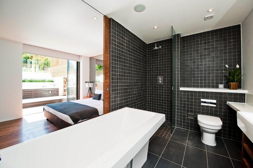 Белоснежная ванна смотрится очень эффектно на фоне черной плитки