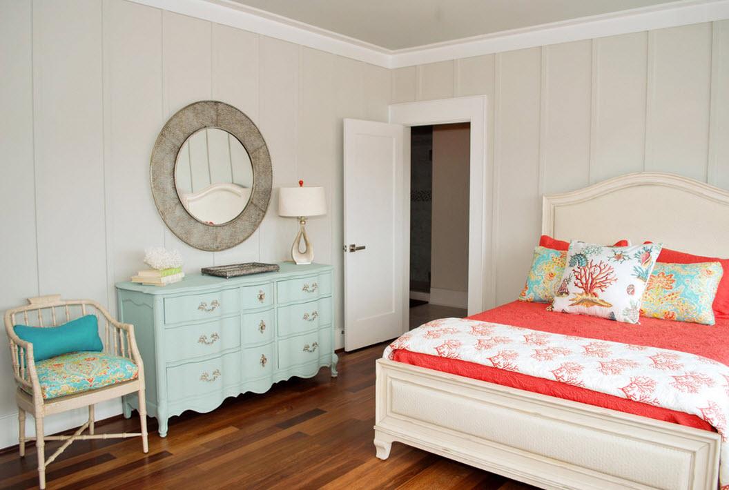 Удачное сочетание бледно-бежевого оттенка стен спальни, нежно-голубого комода и яркого кораллового текстиля