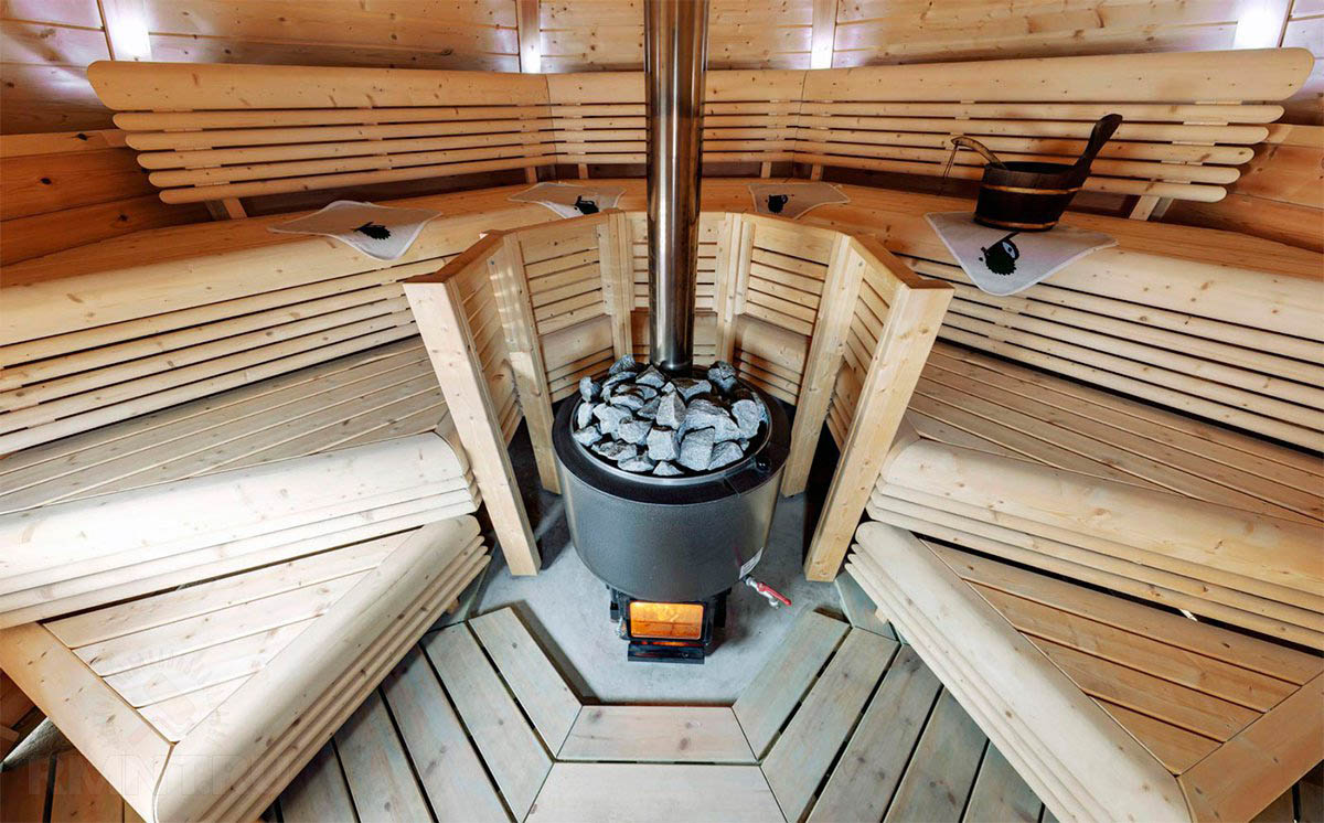 Металлическая печь с чугунным котлом в просторной большой парилке