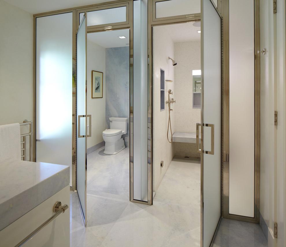Светлое оформление ванной комнаты небольшого размера с дверями из матового стекла