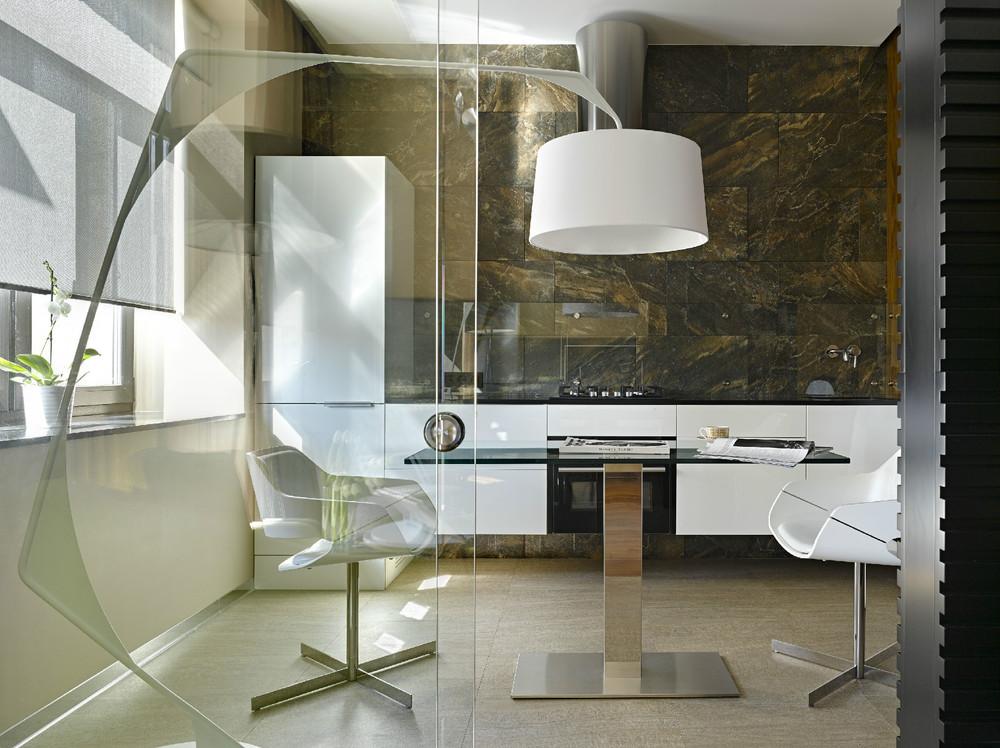 Еще один вариант прозрачной стеклянной защиты над рабочей поверхностью на современной стильной кухне, облицованной натуральным камнем