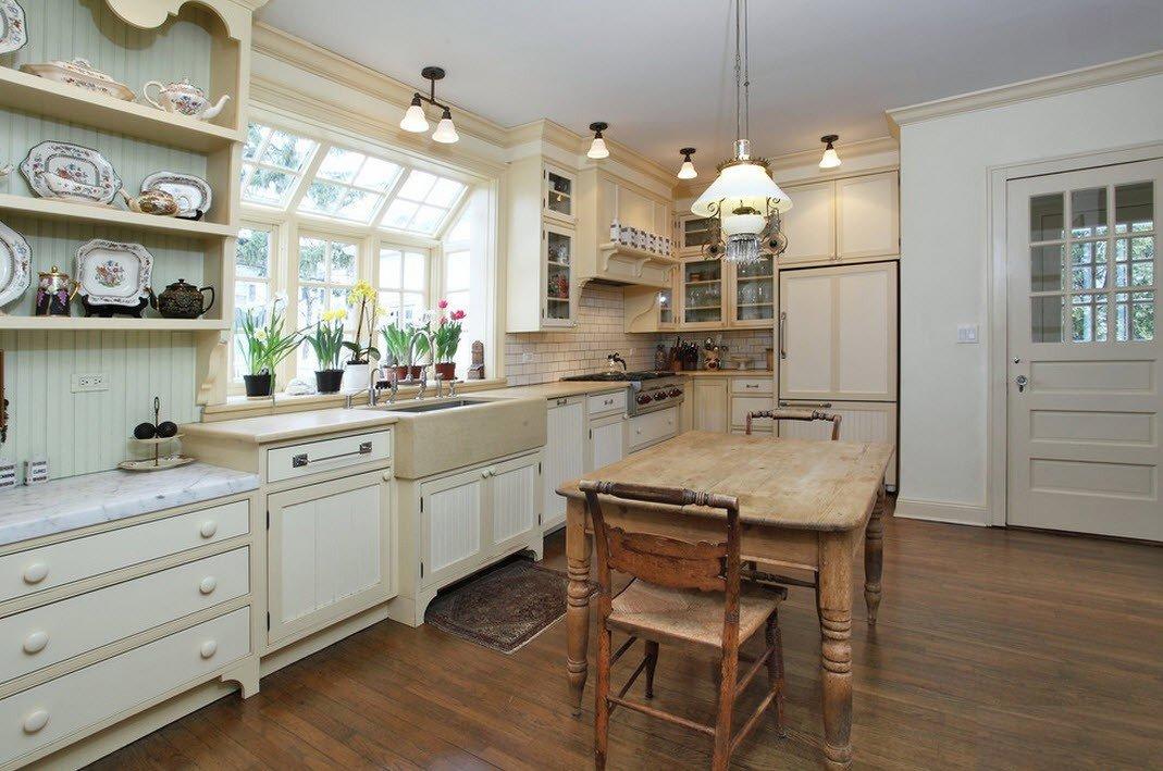Деревянная мебель натурального цвета с элементами ковки на кухне в стиле кантри