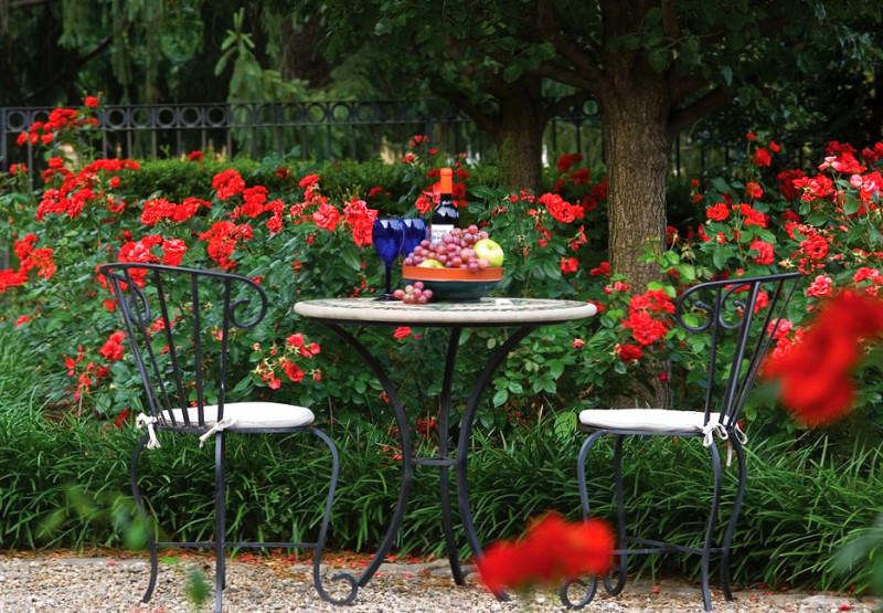 Очень традиционный, и в то же время очень романтичный вид: кованая мебель для импровизированного уголка для двоих в саду с пеларгониями
