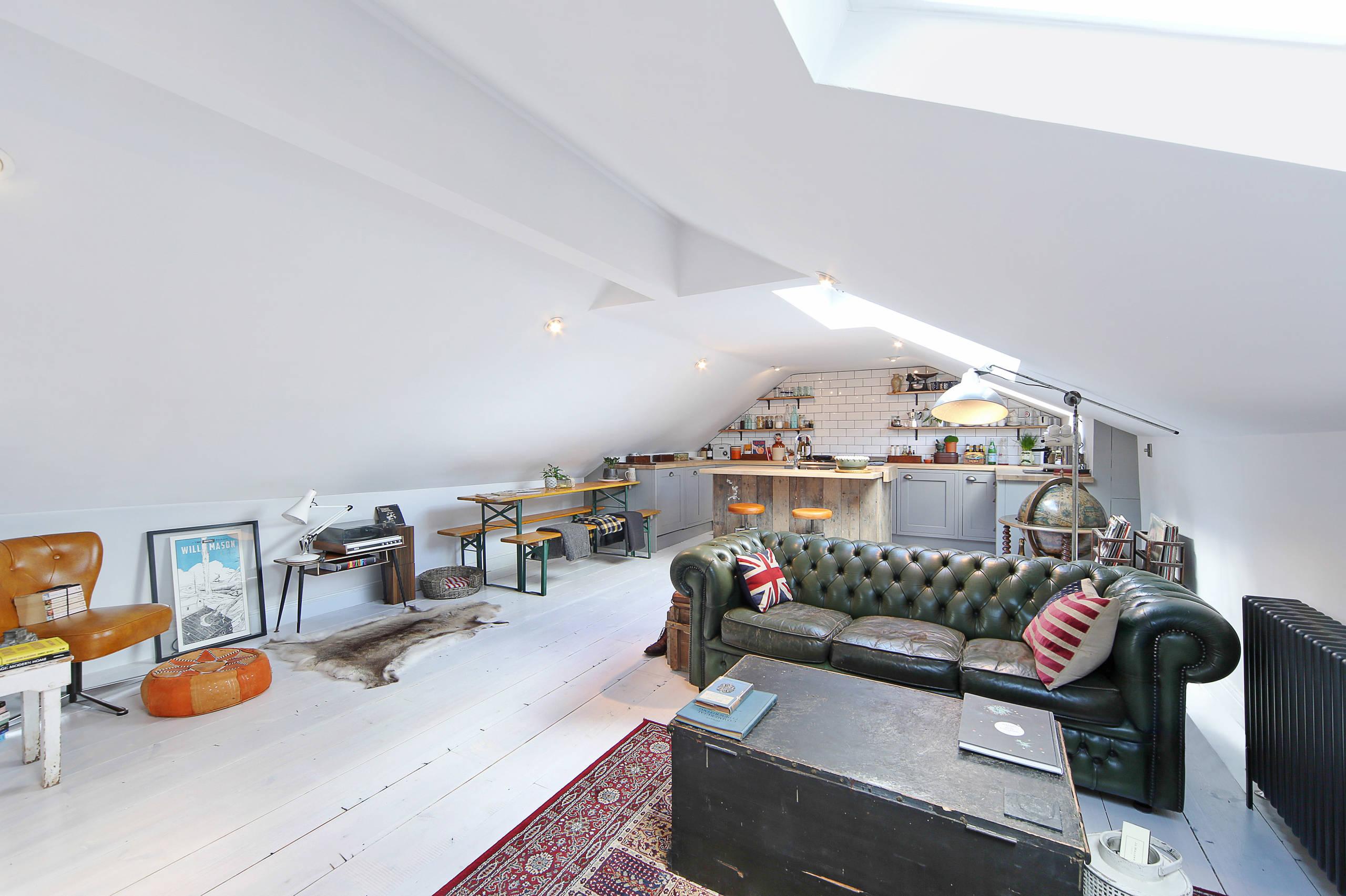 Квартира-чердак с угловатым геометрически-сложным потолком, простой и функциональной мебелью с эффектом состаривания, кожаным диваном в центре комнаты и разными конструкциями освещения